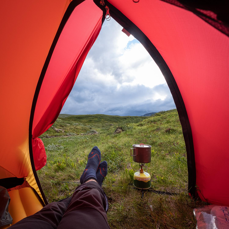 En fjällvandrare lagar mat på gaskök i tältet med utsikt över Jämtlandsfjällen